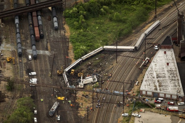 Emergency workers look through the remains of a derailed Amtrak train in Philadelphia, Pennsylvania